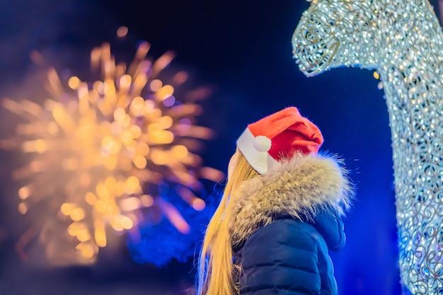 Jovem mulher comemorando o natal e assistindo a fogos de artifício