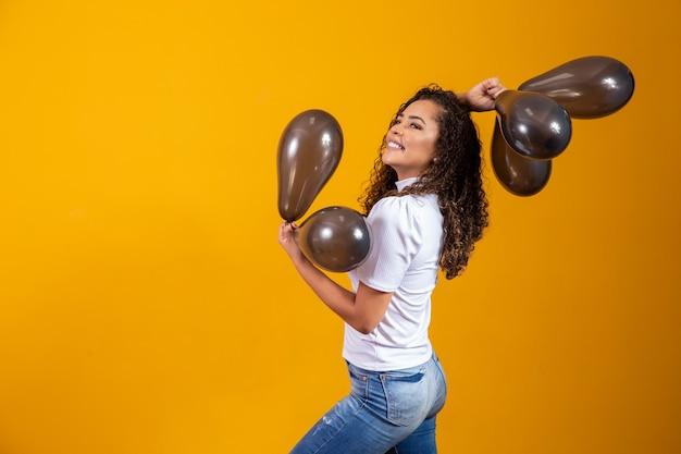 Jovem mulher comemorando sua festa de aniversário com um monte de balões de ar.