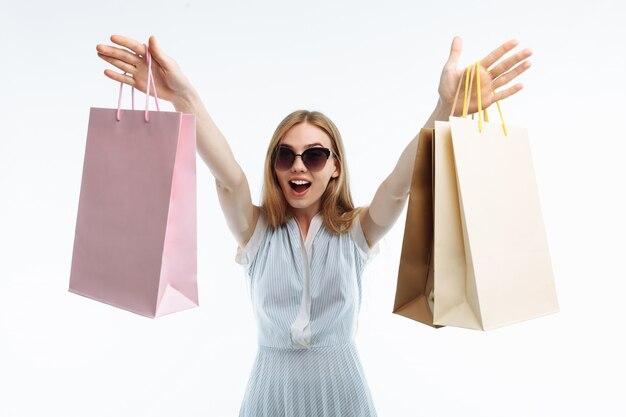 Jovem mulher comercial posando com sacos de presente