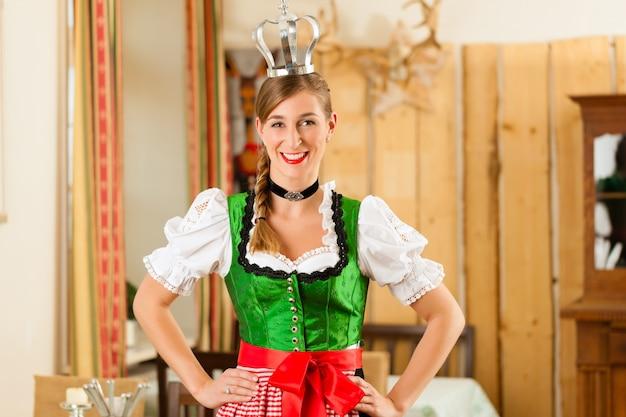 Jovem mulher como rainha no tracht tradicional da baviera no restaurante