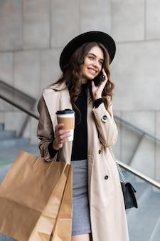 Jovem mulher comprando falando ao telefone e segurando sacolas no centro do shopping