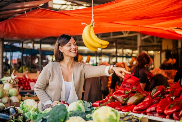 Jovem mulher comprando legumes no mercado.