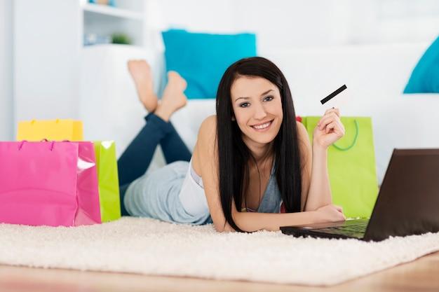 Jovem mulher comprando online e segurando um cartão de crédito