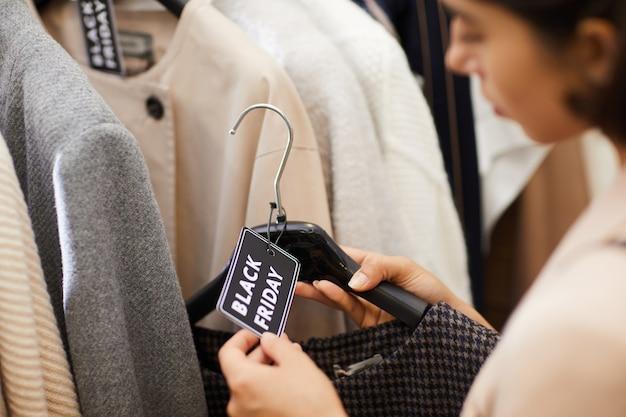 Jovem mulher comprando roupas à venda