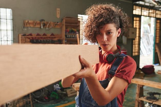 Jovem mulher concentrada com cabelo encaracolado, segurando uma prancha de madeira e medindo seu comprimento com os olhos