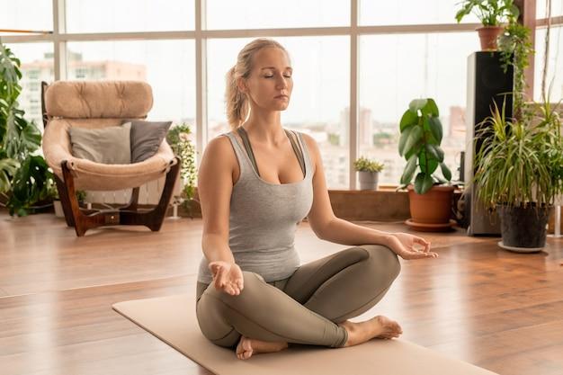 Jovem mulher concentrada em roupas esportivas cruzando as pernas enquanto está sentada na esteira em pose de lótus durante exercícios de meditação em casa