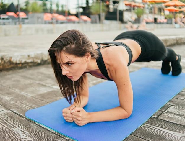 Jovem mulher concentrada em roupas esportivas fazendo exercícios de prancha na esteira ao ar livre