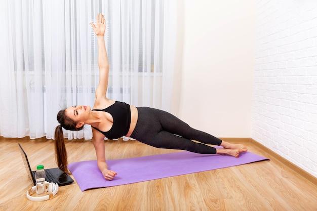 Jovem mulher concentrada fazendo exercícios de ioga usando um laptop