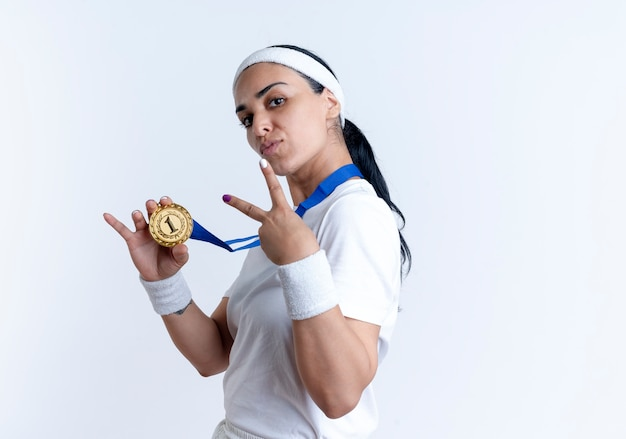 Jovem mulher confiante e desportiva, caucasiana, com fita para a cabeça e pulseiras, segurando a medalha de ouro de lado e gesticulando com a mão da vitória, isolado no espaço em branco com espaço de cópia