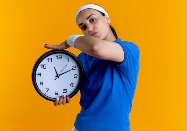 Jovem mulher confiante e desportiva, caucasiana, com fita para a cabeça e pulseiras, segurando um relógio isolado em um fundo laranja com espaço de cópia
