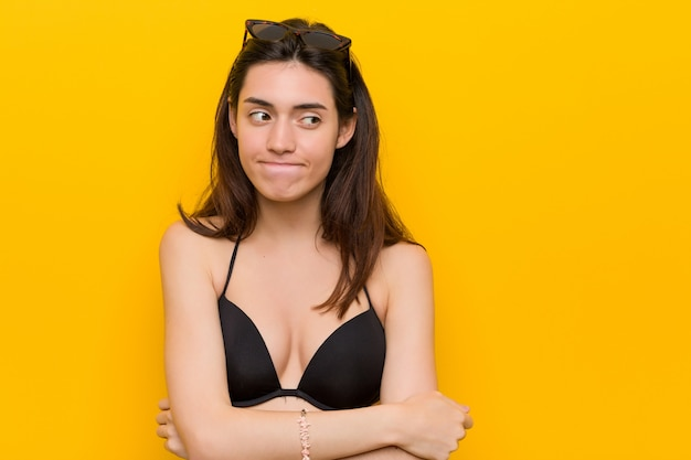 Jovem mulher confusa, vestindo um biquíni contra fundo amarelo