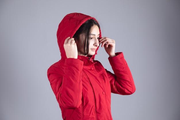 Jovem mulher congelada de mão no chapéu