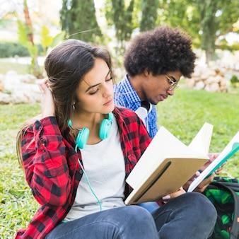 Jovem mulher consideravelmente relaxado que lê um livro com seu amigo no gramado