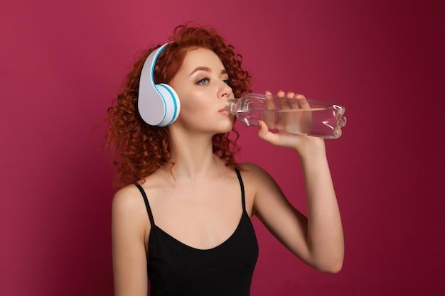 Jovem mulher consideravelmente saudável que bebe a água engarrafada mineral pura