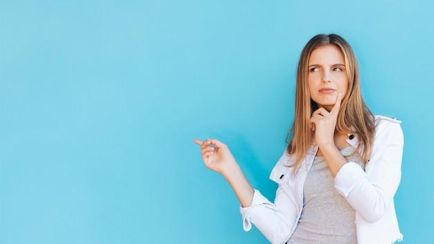 Jovem mulher contemplada apontando o dedo contra o fundo azul