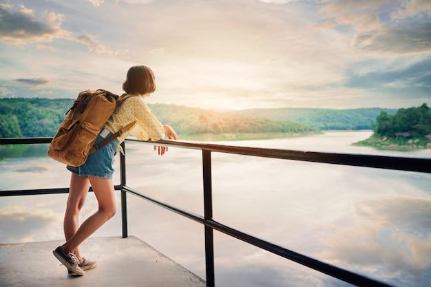 Jovem mulher contemplando o lago