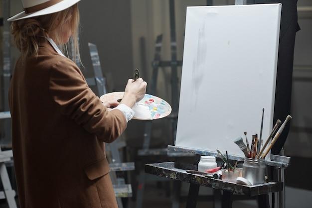 Jovem mulher contemporânea com paleta de cores misturando cores enquanto vai pintar no cavalete com papel em branco em estúdio