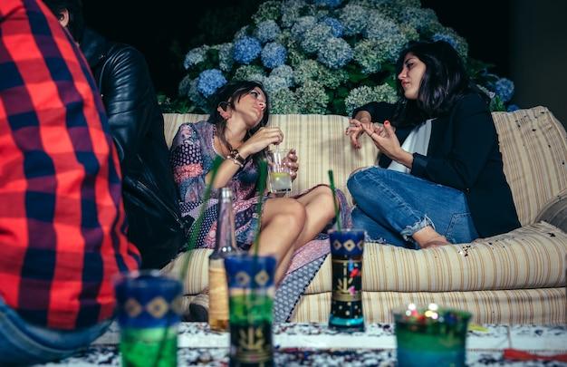 Jovem mulher conversando com uma amiga sentada no sofá em uma festa ao ar livre. conceito de amizade e celebrações.