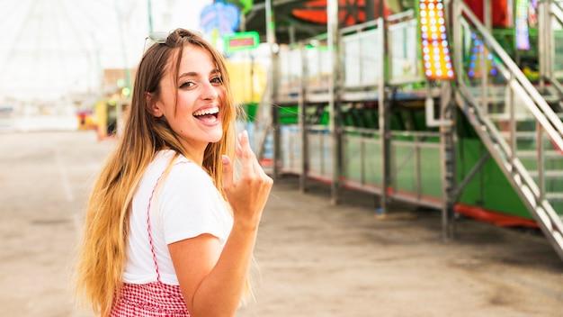 Jovem mulher convidando alguém para vir no parque de diversões
