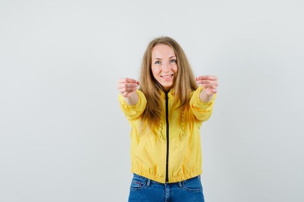 Jovem mulher convidando para entrar na jaqueta amarela e jeans azul e olhando otimista, vista frontal.
