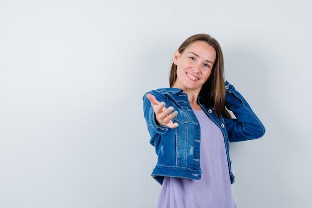 Jovem mulher convidando para vir, mantendo a mão atrás da cabeça em t-shirt, jaqueta jeans e parecendo alegre, vista frontal.