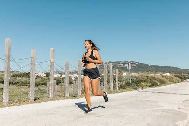 Jovem mulher correndo ao longo da estrada a sorrir