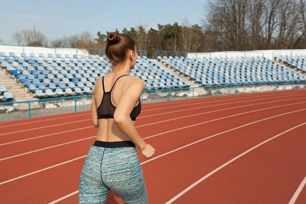 Jovem mulher correndo durante a manhã de sol na pista do estádio