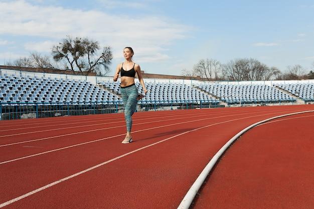 Jovem mulher correndo durante a manhã ensolarada na pista do estádio