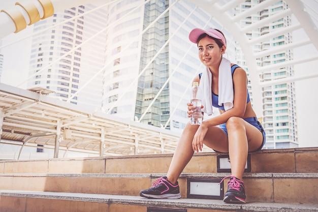 Jovem mulher correndo e bebendo água