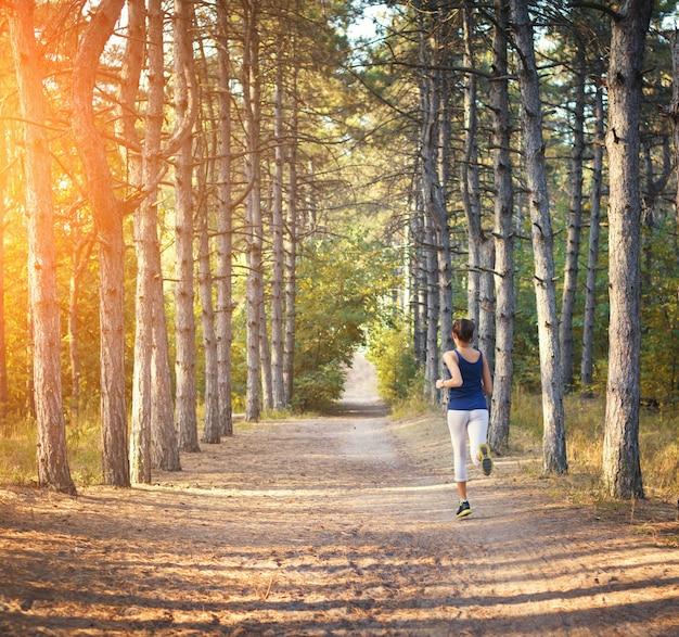 Jovem mulher correndo em uma estrada rural na floresta