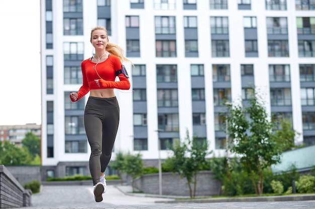 Jovem mulher correndo na rua da cidade