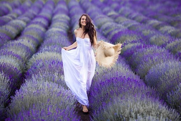 Jovem mulher correndo no campo de lavanda. mulher bonita em fundo floral verão