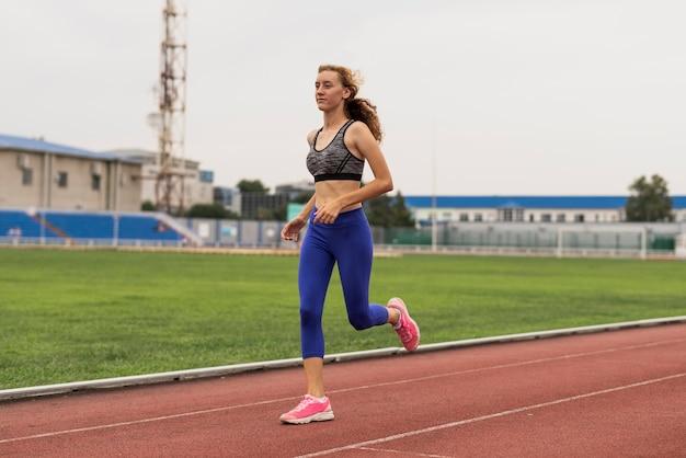 Jovem mulher correndo no estádio