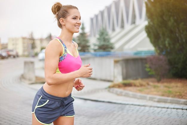 Jovem mulher correndo ou correndo ao ar livre. a cidade oferece muitas oportunidades para fazer jogging