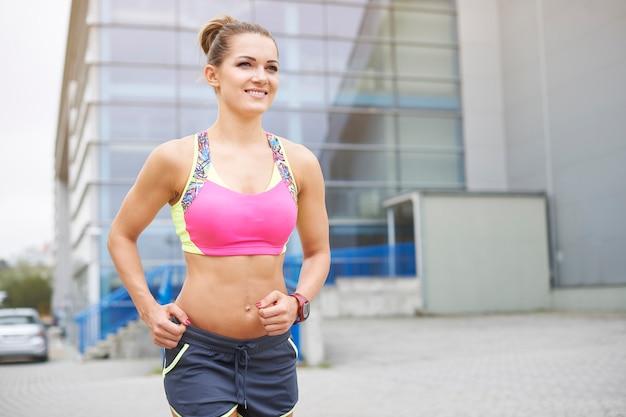 Jovem mulher correndo ou correndo ao ar livre. de manhã é a melhor hora do dia para correr