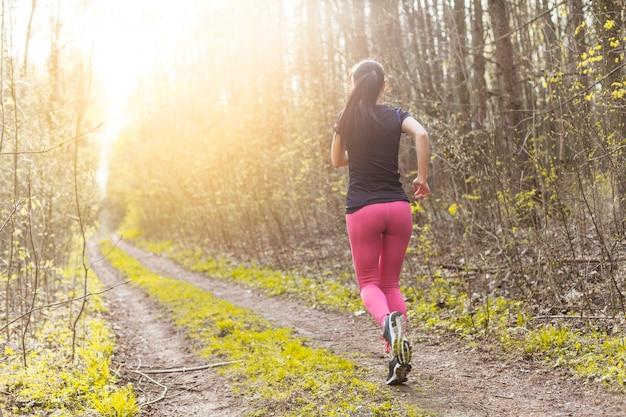 Jovem mulher correndo pela floresta