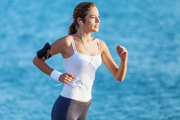 Jovem mulher correndo pela praia com o mar azul no fundo