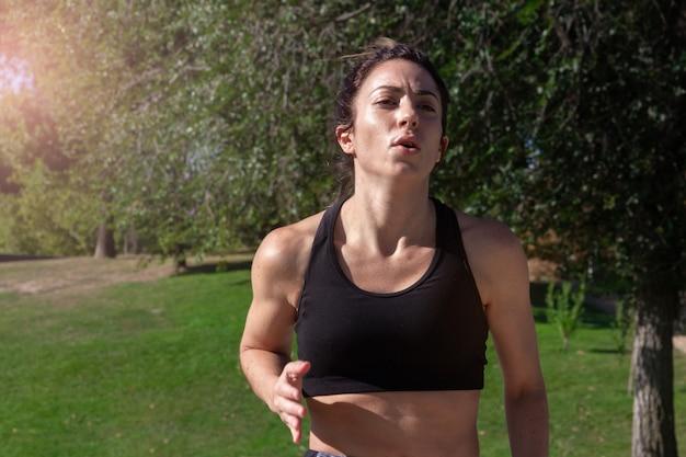 Jovem mulher correndo por um parque em um dia ensolarado. estilo de vida saudável. foco seletivo.