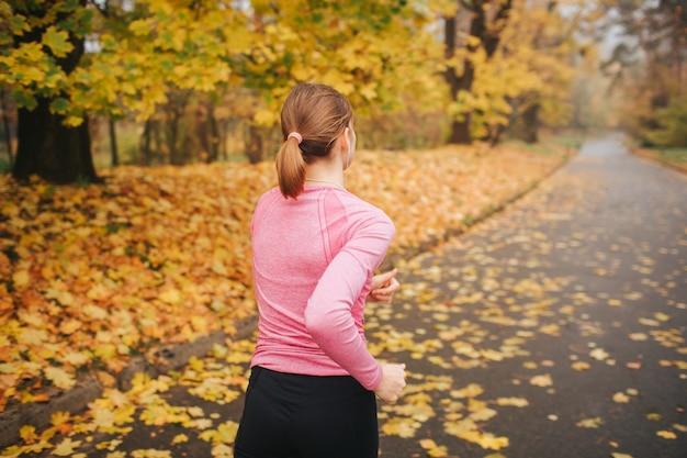 Jovem mulher correndo sozinho no parque. é outono lá fora. ela corre na estrada.