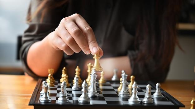 Jovem mulher cortada do tiro que empalidece o tabuleiro de xadrez na tabela.