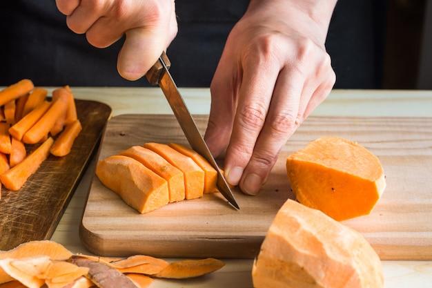 Jovem mulher cortando com faca batata-doce em fatias cascas na mesa de madeira