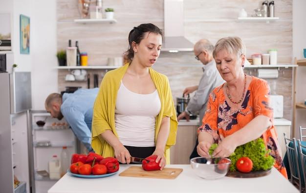 Jovem mulher cortando o pimentão para a salada, enquanto ajudava a mãe a preparar a salada durante o almoço.