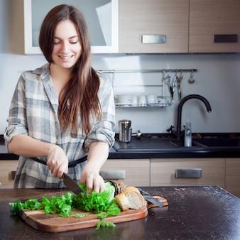 Jovem mulher cortar uma salada para sua família