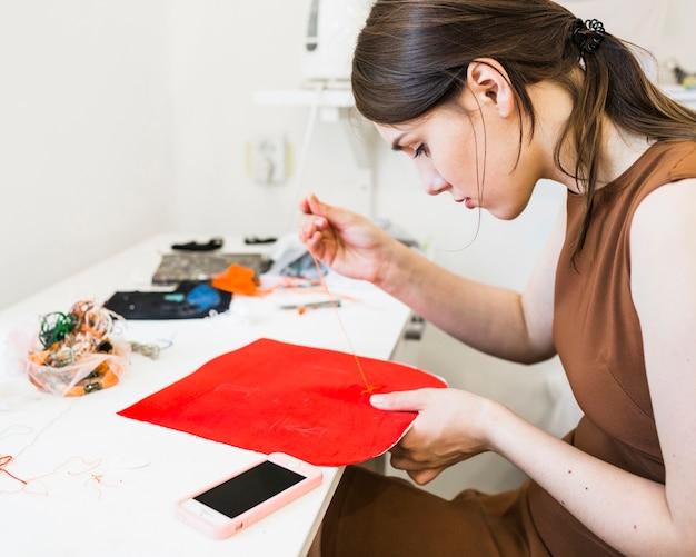 Jovem mulher costura pano vermelho com agulha