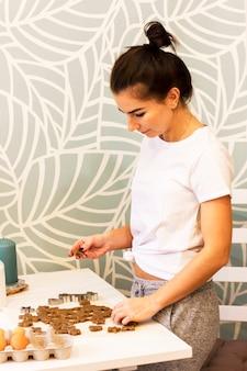 Jovem mulher coze biscoitos de gengibre na cozinha