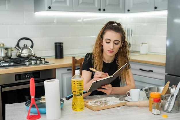 Jovem mulher cozinhando bolo com farinha, lendo a receita do bloco de notas na mesa da cozinha. comida saudável