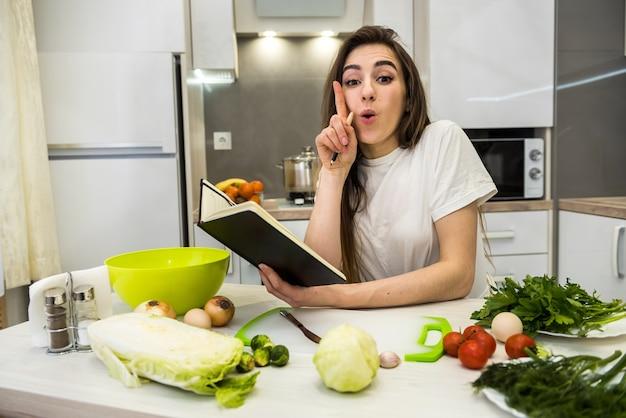 Jovem mulher cozinhando comida usando um bloco de notas como ajuda em sua cozinha.