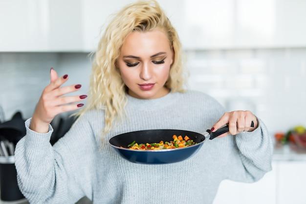 Jovem mulher cozinhando e cheirando comida na frigideira na cozinha em casa.