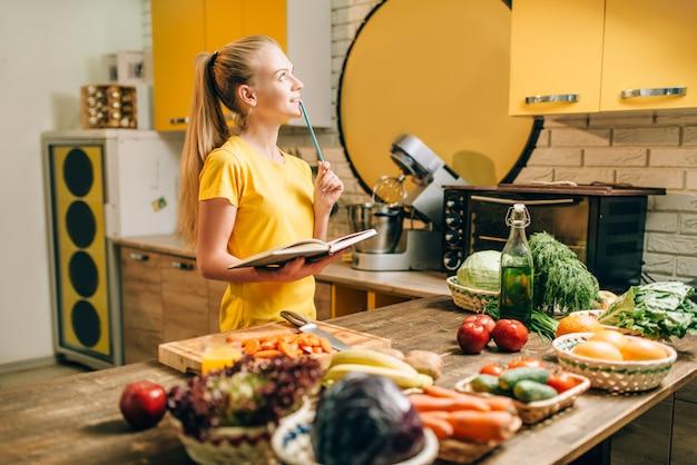 Jovem mulher cozinhando em receitas, alimentos ecológicos saudáveis. dieta vegetariana, frutas e vegetais frescos