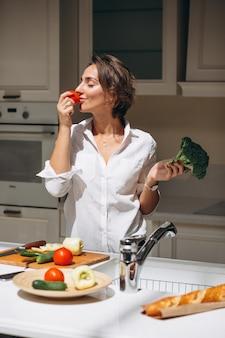 Jovem mulher cozinhando na cozinha pela manhã
